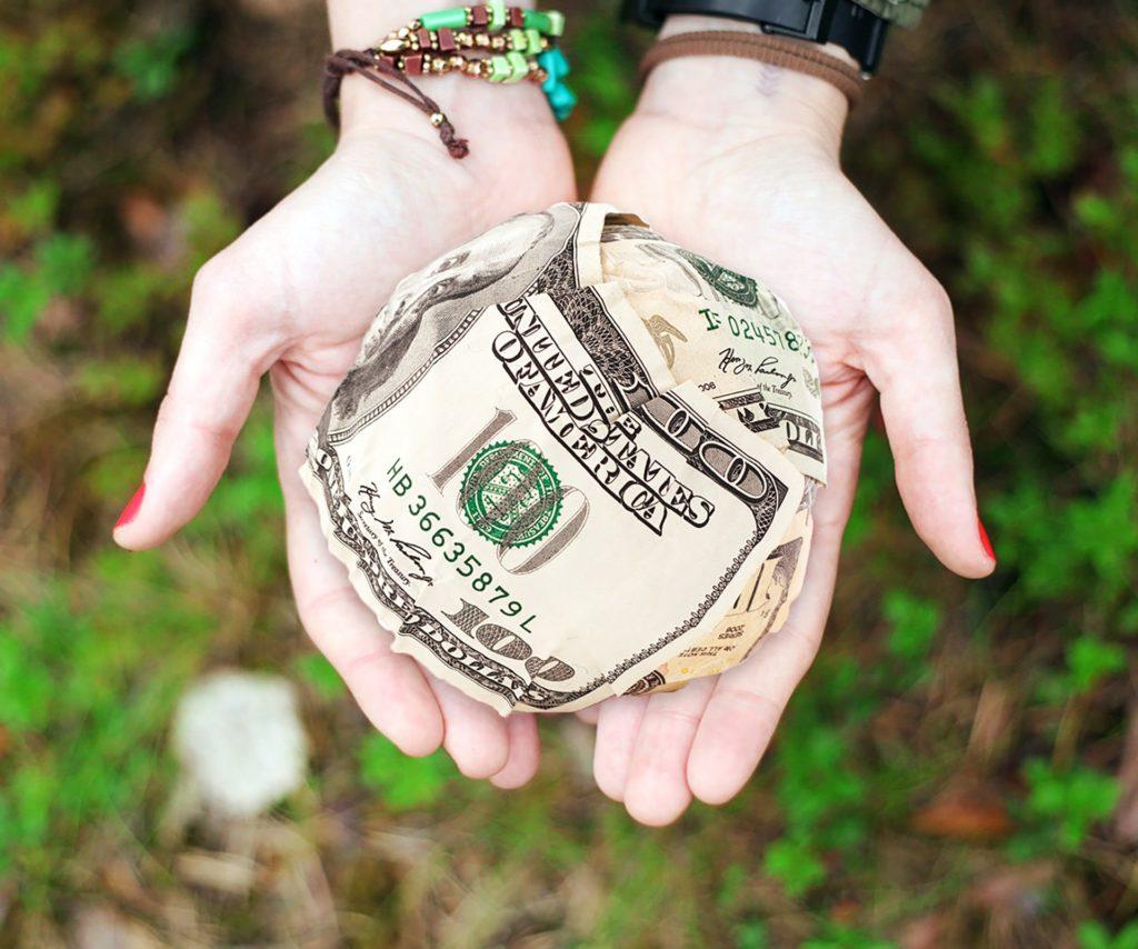 Bracelets and crumpled Money in hand - Katie Ramadan